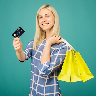 Happy girl in a checkered blouse holds credit card and shopping bags on blue background