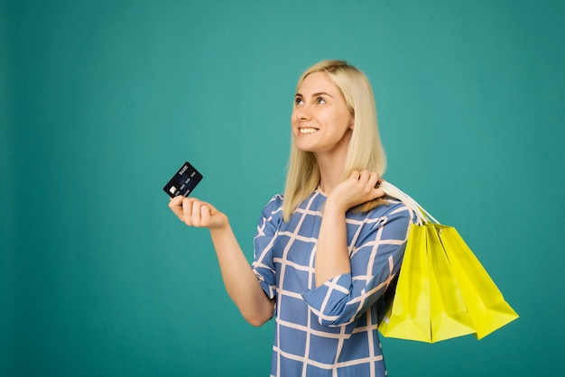 Happy girl in a checkered blouse holds credit card and shopping bags