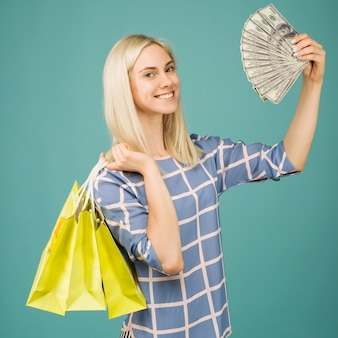 Happy girl in a checkered blouse holds one hundred dollars bills and shopping bags