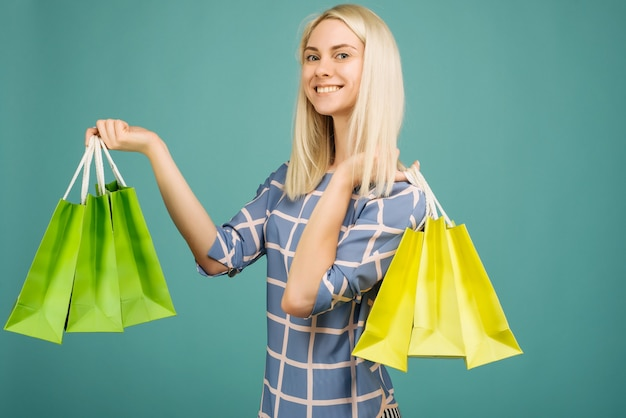 Happy girl in a checkered blouse holds shopping bags