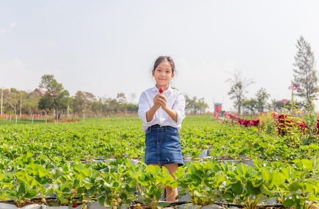 Happy girl child holding fresh red organic strawberries in the garden