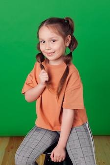 아름다움 표정으로 행복 한 여자 아이 캐주얼 패션 스타일 녹색 벽, 헤어 스타일에 긴 머리 케이블을 잡아.
