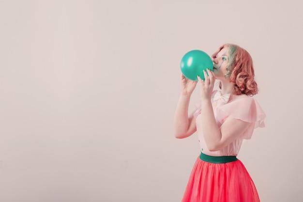 Счастливая девушка клоун с зеленым шаром на белом фоне