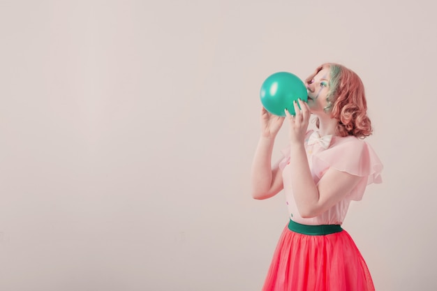 Happy girl clown with green balloon on white background
