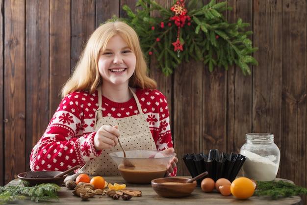 Счастливая девушка готовит рождественский торт