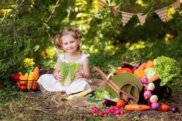幸せな少女は、自然に野菜のサラダを調理します。小さな庭師が野菜を収穫します。