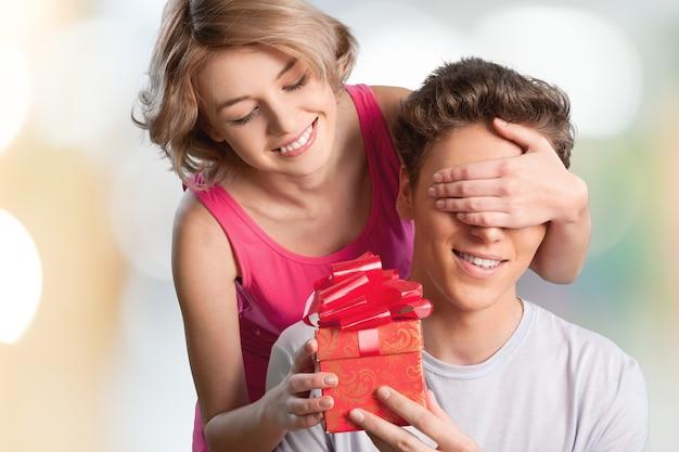 남자친구의 눈을 손으로 가리고 선물을 주는 행복한 소녀