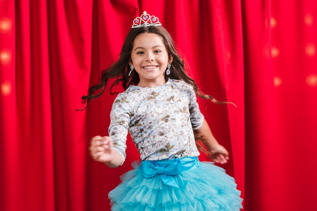 Happy girl in cute dress dancing in front of red curtain