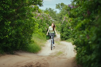 Happy girl cyclist riding on a mountain bike outside. Adventure travel.