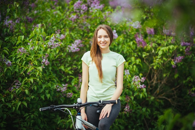 Ciclista ragazza felice in piedi con una mountain bike e. viaggio avventuroso.
