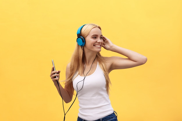 Happy girl dancing and listening to the music isolated on a yellow background