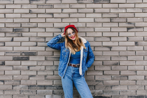Happy girl in denim outfit standing in front of brick wall. outdoor photo of caucasian young lady wears jeans and red hat expressing positive emotions.