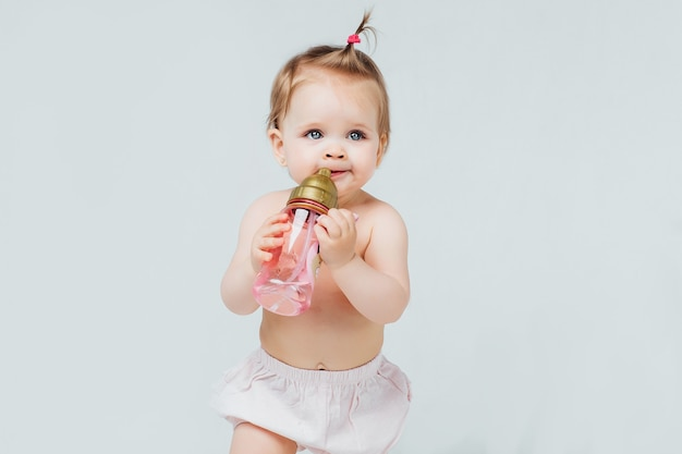 Happy girl in diaper with cute hairstyle, holds bottle of milk