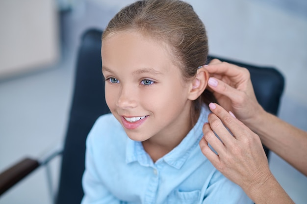 Happy girl and doctors hands putting on hearing aid