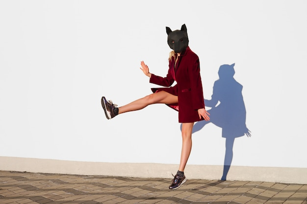 Happy girl in dog head mask jumping close to the wall with reflection on it