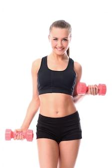 Счастливая девушка делает упражнения с гантелями
