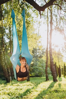 Happy girl doing fly yoga  closed eyes outdoors