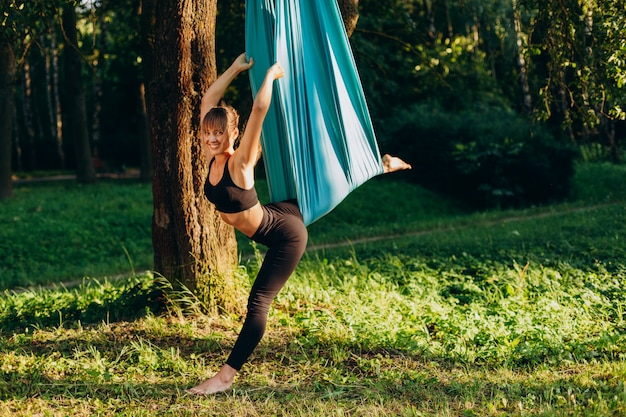 Happy girl doing fly yoga outdoors.