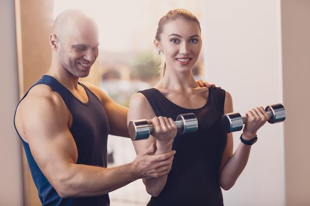 Happy girl doing strength exercise dumbbell hands