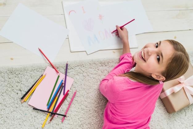 Счастливая девушка рисует я люблю маму на бумаге