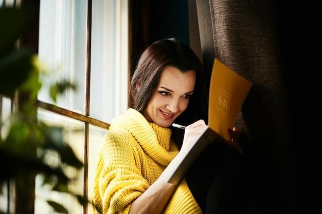 幸せな女の子は彼女のノートに何かを描く