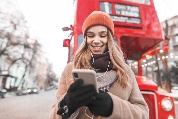 따뜻한 옷을 입은 행복한 소녀와 장갑은 그녀의 손에 스마트 폰을 들고 거리에 서서 헤드폰과 미소로 음악을 듣고