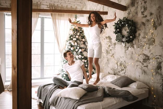 흰색 티셔츠와 반바지를 입은 행복한 소녀가 새해 나무, 선물, 양초로 장식된 아늑한 방에 앉아 있는 남자 옆에 침대 위로 뛰어오르고 있습니다.