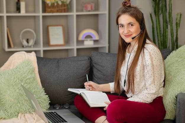 Счастливая девушка электронного обучения с ноутбуком и наушниками, сидя на диване в гостиной дома