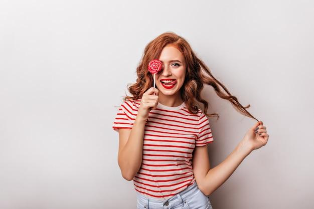 Ragazza felice che mangia caramelle e gioca con i suoi capelli ricci. ispirata donna allo zenzero con lecca-lecca.