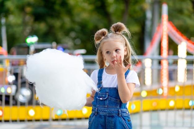 Счастливая девушка ест сладкую вату в парке развлечений