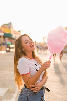 Happy girl eating cotton candy