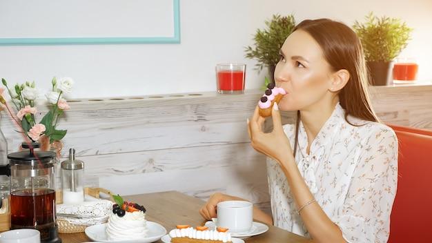 행복한 소녀는 현대적인 달콤한 가게에서 딸기와 함께 맛있는 케이크를 먹는다