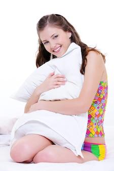 幸せな女の子は白い枕を受け入れる