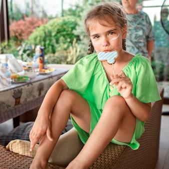 屋外の誕生日パーティーの夏のピクニック中にテラスでカラフルなケーキを楽しんで幸せな女の子