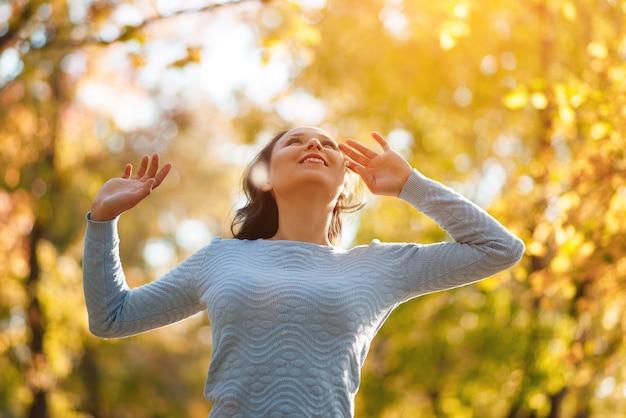 Счастливая девушка наслаждается жизнью и свободой осенью на природе. осенняя концепция