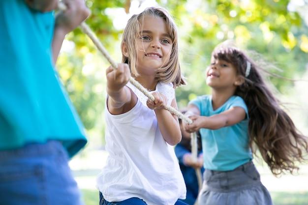Счастливая девушка, наслаждаясь мероприятиями на свежем воздухе, играя в перетягивание каната с друзьями. группа детей, весело проводящих время в парке. концепция детства