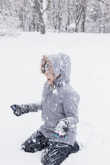 Happy girl enjoying snowfall at forest in winter