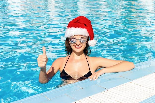 크리스마스 모자에 행복 한 여자 얼굴은 수영장, 여름 휴가에 엄지 손가락을 보여줍니다