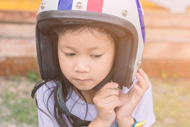 Happy girl fastenings motorbike helmet
