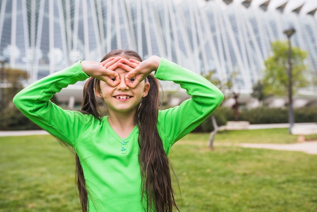 Happy girl forming goggle with her finger standing in park