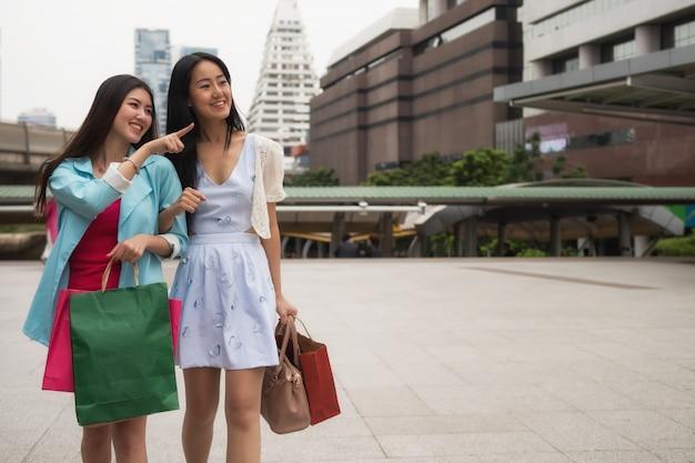 도시에서 쇼핑하는 행복 한 여자 친구