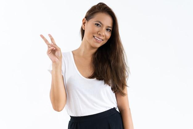 Happy girl gesturing peace