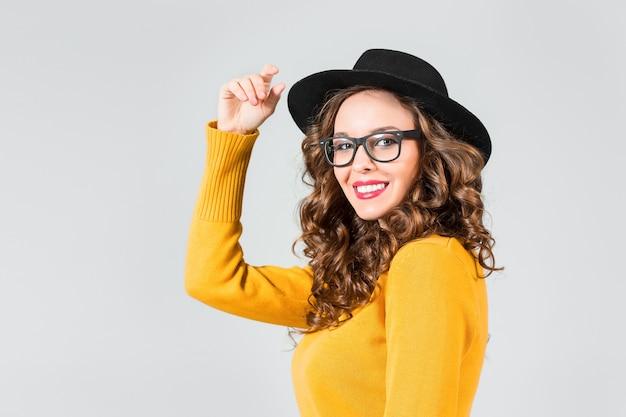 La ragazza felice in occhiali e cappello sulla parete grigia dello studio