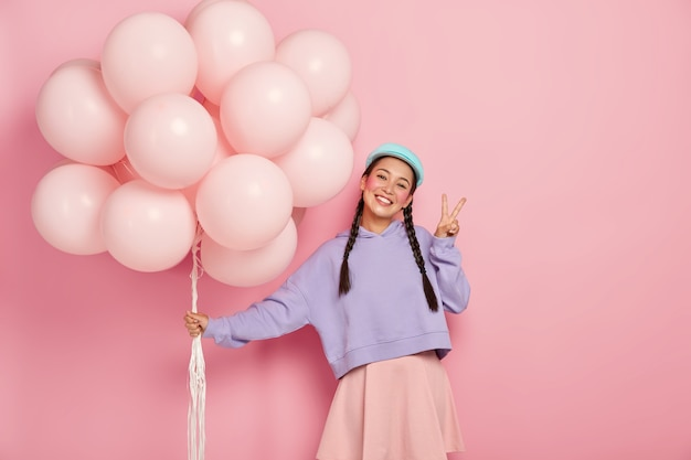 Happy girl greets friends on balloon party, has two plaits, wears purple sweater and skirt, makes peace gesture, stands against pink wall