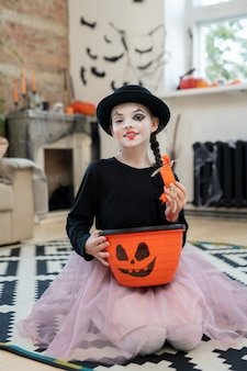 Happy girl in halloween attire holding basket with treats