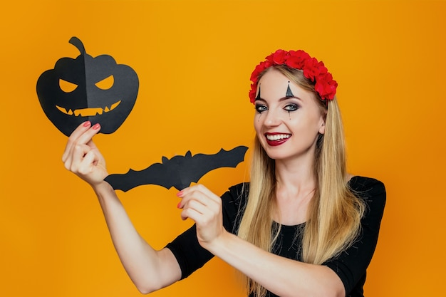 Happy girl in halloween costume holding pumpkin and bat festive paper decorations isolated on orange