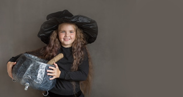 Happy girl in halloween witch costume brew a potion