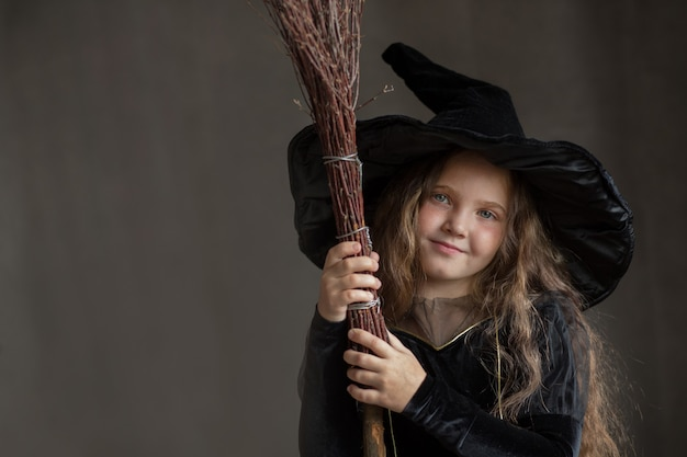 Happy girl in halloween witch costume on gray background