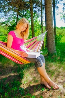Happy girl in a hammock reading a book on nature in the park