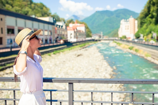 Happy girl at hat on the embankment of a mountain river in a european city.